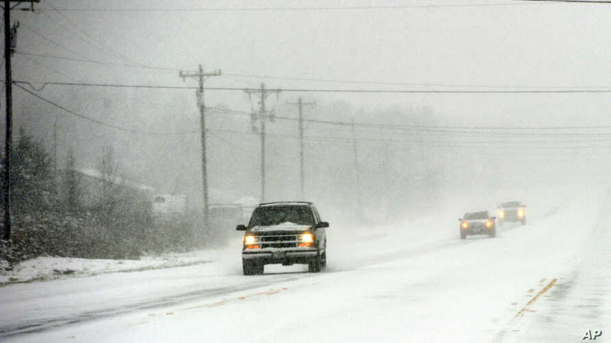 Drivers navigate U.S. Hwy 25 in southern Greenville County, as snow falls near Greenville, S.C., Feb. 12, 2014.