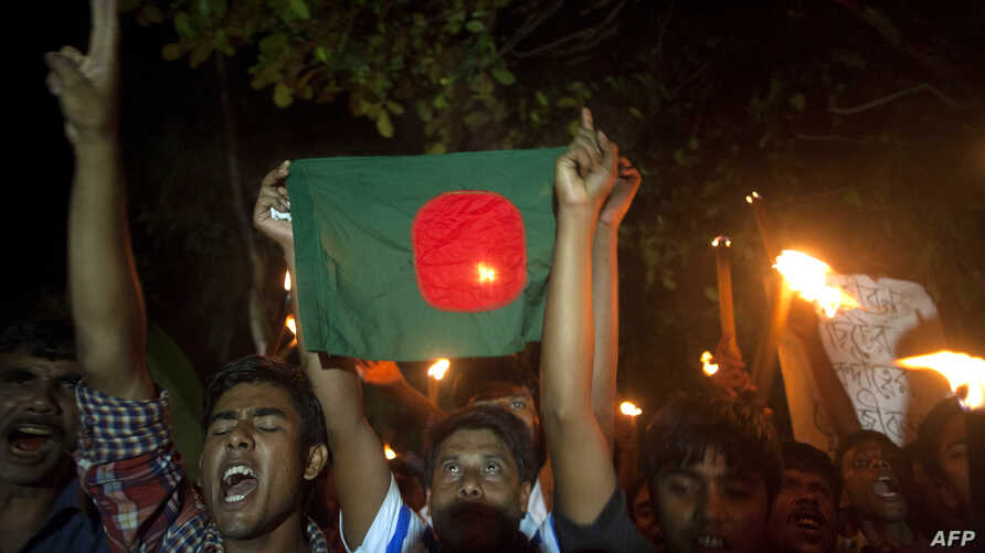 Former Indian enclave residents carry torches and a Bangladesh flag as they celebrate at Dasiarchhara, Kurigram in Bangladesh, as Bangladesh and India swapped tiny islands of land, ending one of the world's most intractable border disputes, Aug. 1, 2