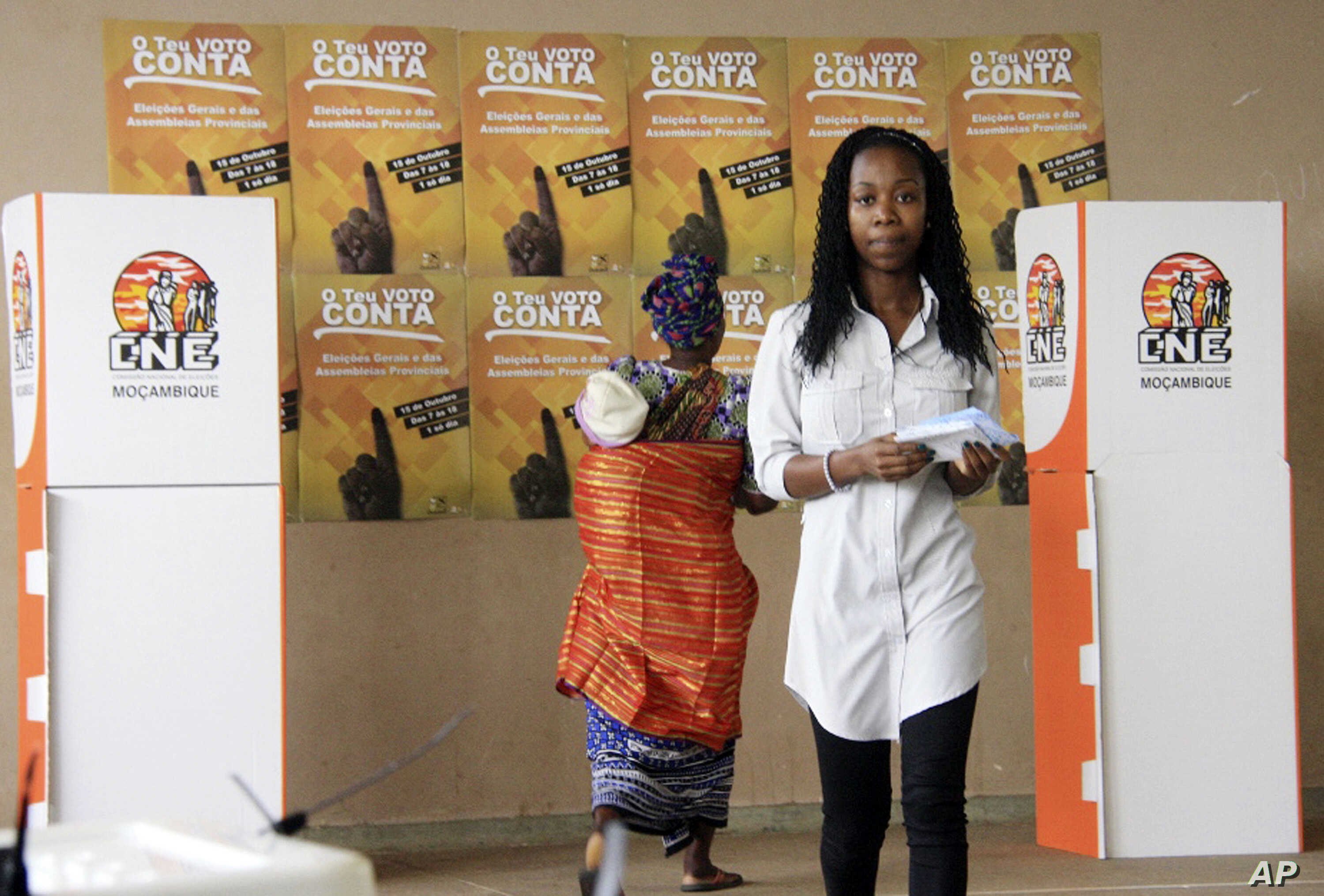 Voters prepare for casting their votes at a polling station as the country goes to the polls in Maputo, Mozambique, Oct. 15, 2014.
