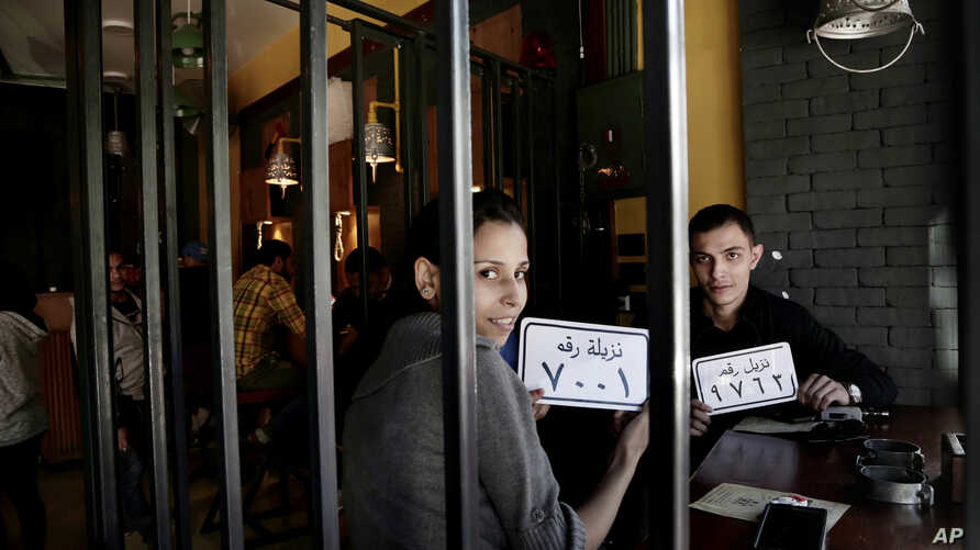 Customer Amr El Gohary, right, and his friend pose for a photograph with plastic plaques that translate to inmates with numbers, as they wait for their food, at prison-themed restaurant 'Food Crime' in the Nile Delta city of Mansoura, 110 kilometers