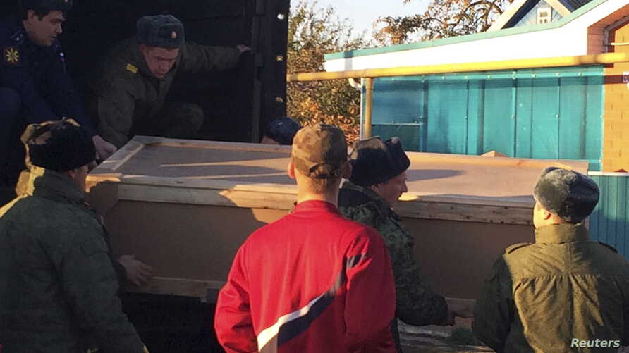 Russian servicemen unload a coffin containing the body of Vadim Kostenko, a member of the Russian air force's support staff in Syria, from a truck near his family's house in Grechanaya Balka, Russia, Oct. 27, 2015.