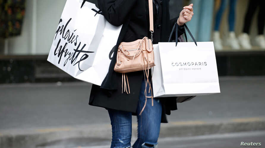 FILE - A customer carries shopping bags with purchases outside a department store in Paris, France.