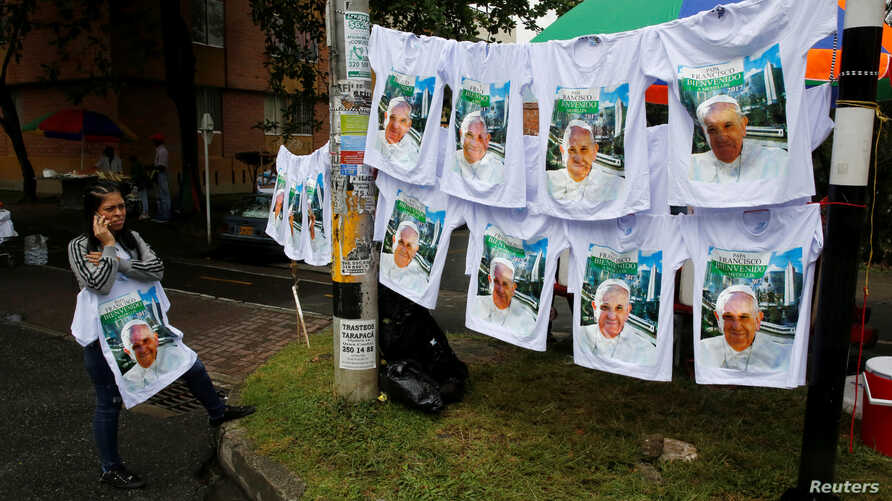 A woman sells T-shirts with images of Pope Francis as the faithful arrive for a holy mass  Saturday by Pope Francis outside Olaya Herrera Airport, Medellin, Colombia, Sept. 8, 2017.