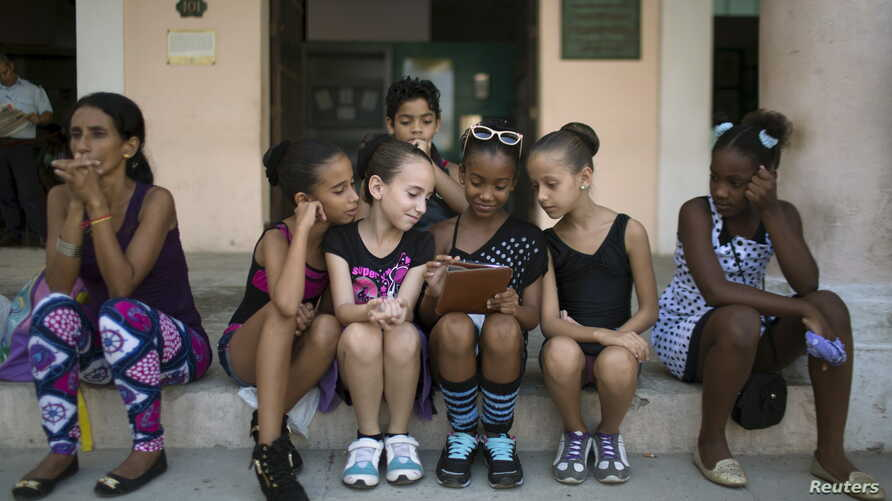 Children play with a tablet before performing at the first day of a contemporary urban dance festival in downtown Havana, April 15, 2015.