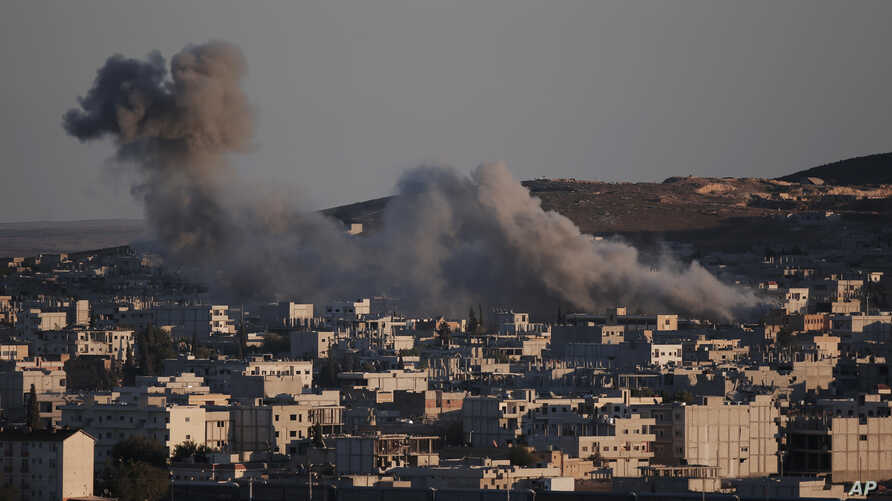 Thick smoke from an airstrike by the US-led coalition rises in Kobani, Syria, as seen from a hilltop on the outskirts of Suruc, at the Turkey-Syria border, Oct. 21, 2014.