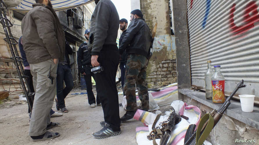 Free Syrian Army fighters stand by their weapons in the besieged area of Homs, March 9, 2013.