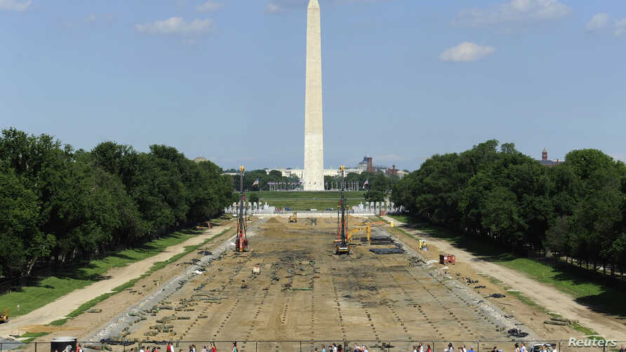 Tourists walk past work underway to reconstruct the Lincoln Memorial Reflecting Pool on the National Mall in Washington, May 11, 2011.