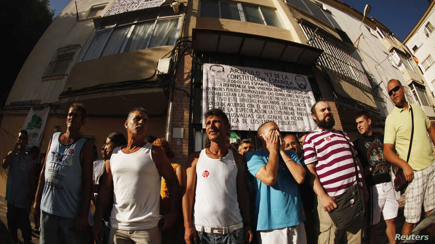 """Members of """"Stop Desahucios"""" [Stop evictions], 15M and """"Afectados X la Hipoteca"""" [Mortgage Victims Platform] block the door of the building of Maria Jose Lopez and her husband Savador's flat, before being evicted for failing to pay their mortgage, in"""