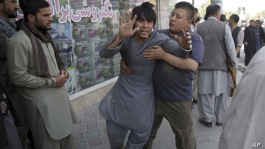 A shocked man shouts slogans against President Ghani after he ran out of the Shiite mosque during an ongoing attack, Kabul, Afghanistan, Aug. 25, 2017.