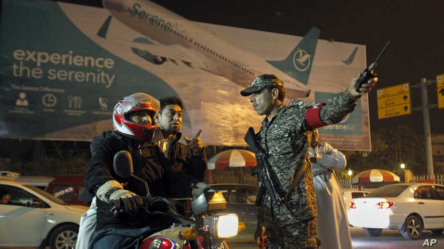 An airport security officer directs a motorcyclist at the entrance to the Benazir Bhutto International Airport in Islamabad, Pakistan, Dec. 7, 2016.