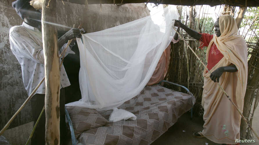 A Sudanese women gets help setting up a bed net (file photo)