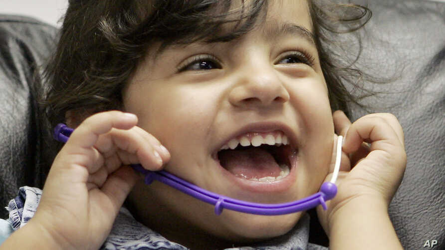 FILE - Three-year-old Amina of Iraq laughs during a hearing test.