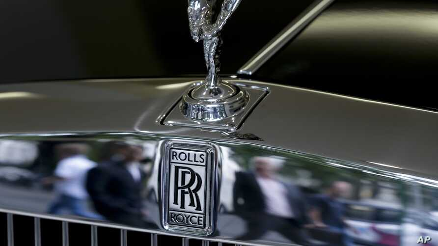 FILE - Pedestrians are reflected in the chrome work under the Spirit of Ecstasy on the front of a Rolls- Royce car, in a show room in London, July 8, 2014.