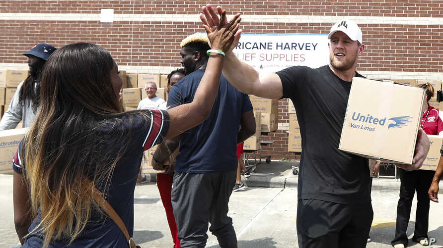 FILE - In this Sept. 3, 2017, file photo, Anna Ucheomumu, left, high fives Houston Texans defensive end J.J. Watt after loading a car with relief supplies to people impacted by Hurricane Harvey, in Houston. J.J. Watt is being honored by the NFL Playe