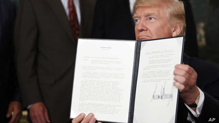 President Donald Trump holds up a signed memorandum calling for a trade investigation of China, Aug. 14, 2017, in the Diplomatic Reception Room of the White House in Washington.
