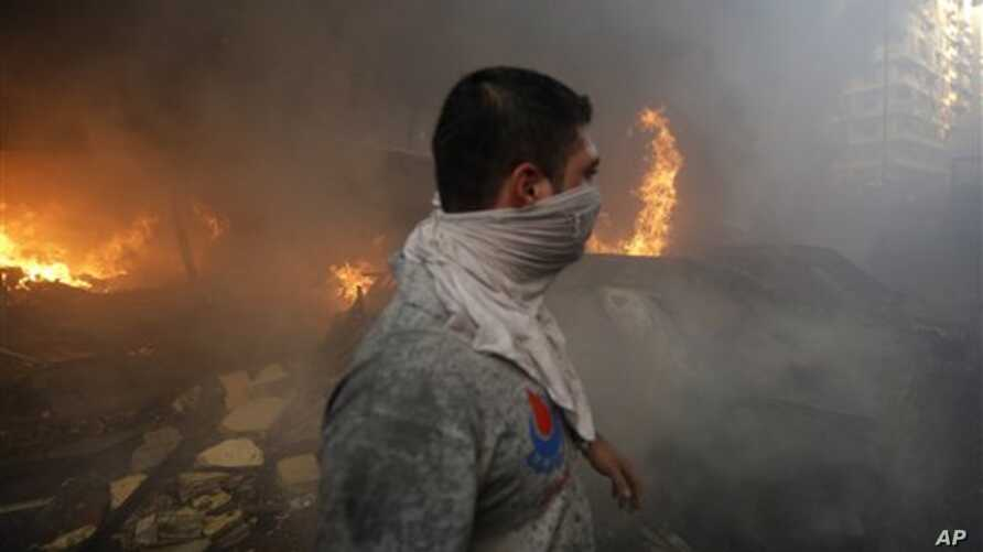 A Hezbollah civil defense worker walks past a burned car at a car bomb in the southern suburb of Beirut, Lebanon, Thursday, Aug. 15, 2013. The powerful car bomb ripped through a southern Beirut neighborhood that is a stronghold of the militant group