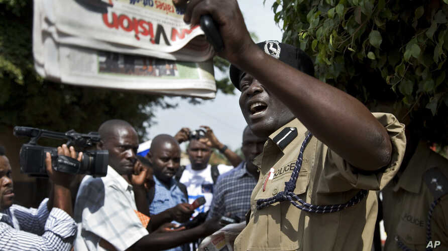 A Ugandan policeman holds up a newspaper, just before police fired tear gas to disperse the demonstration in downtown Kampala, Uganda. Some local activists are writing and distributing books that they hope can be as effective as placards, (File photo