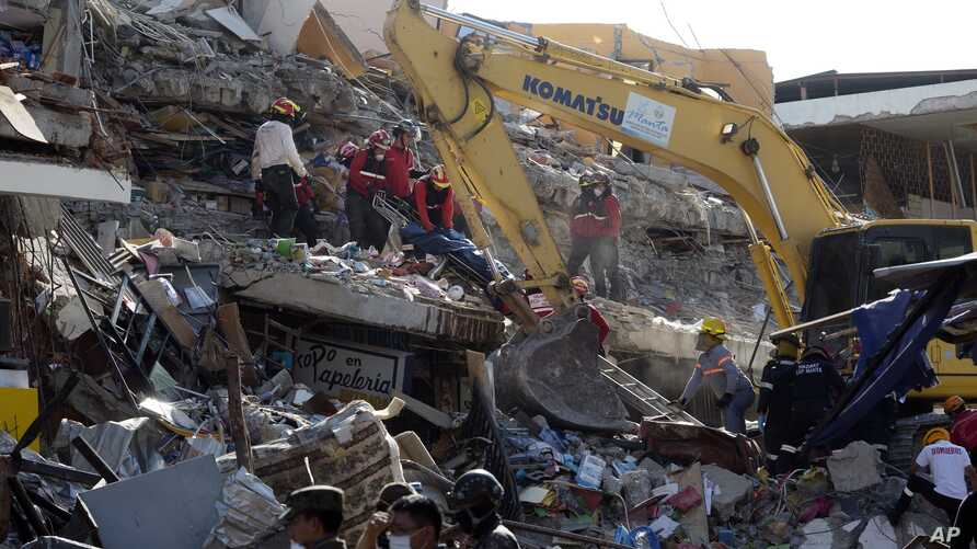 Rescue workers recover a body from the rubble a bulldozer removes the debris of a collapsed building felled by a 7.8-magnitude earthquake, in Manta, Ecuador, April 19, 2016.
