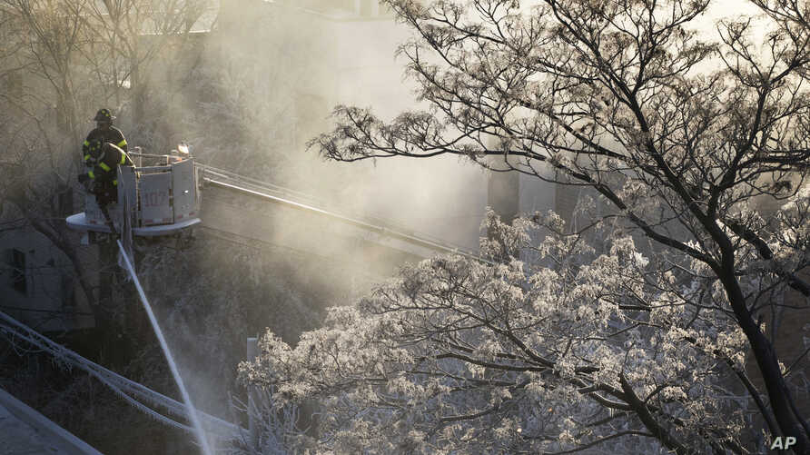 Ice forms on tree branches as firefighters battle a blaze in a commercial building in the Bedford Stuyvesant neighborhood of Brooklyn, New York, Jan. 31, 2019.