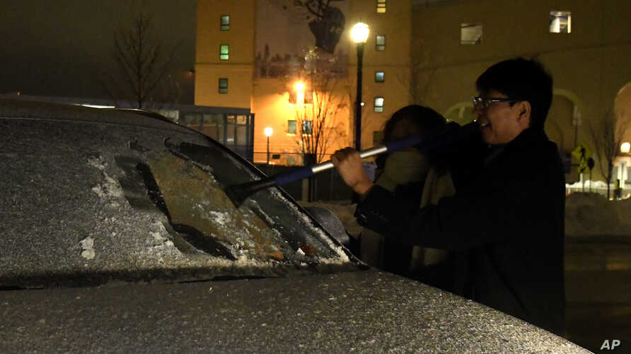 Hongxin Dong scraps ice off his car, Jan. 22, 2019, in Evanston, Illinois.