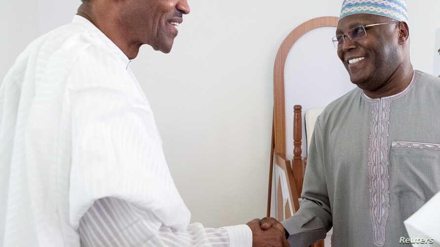 Nigeria's President Muhhamadu Buhari (L) is joined by former Vice President Alhaji Atiku Abubakar as they attend the Jumaat Prayers after Alhaji Atiku Abubakar returned from medical treatment overseas, in Abuja, Nigeria. Buhari's cabinet is finally b