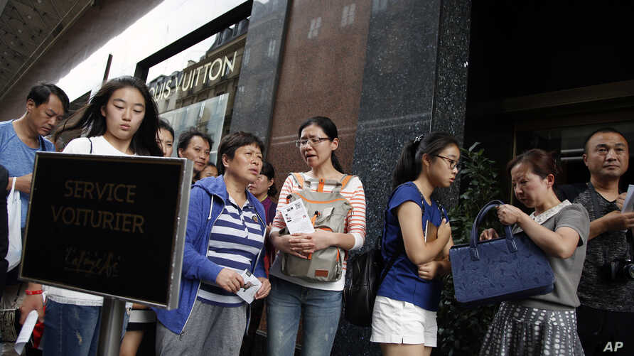 Chinese tourists queue outside the Galeries Lafayette general store in Paris, France, Wednesday, Aug. 26, 2015.