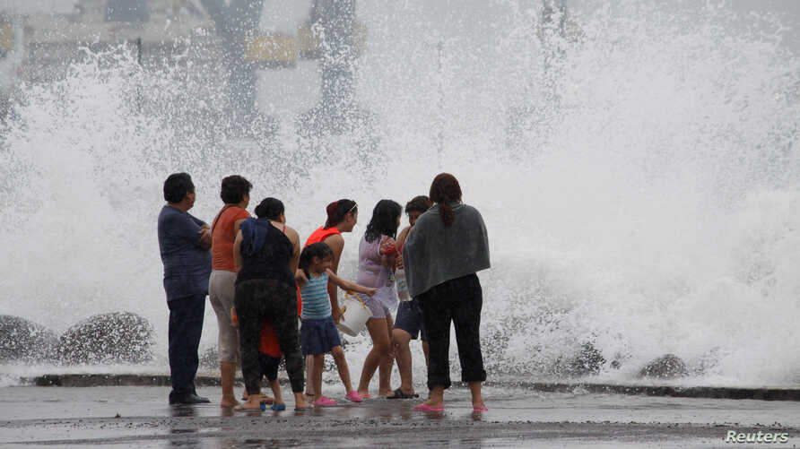 A family reacts to waves breaking over the seawall ahead of Hurricane Franklin in Veracruz, Mexico, Aug. 9, 2017.