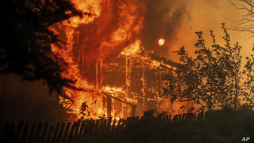 Flames consume a home as the River Fire tears though Lakeport, Calif., July 31, 2018.
