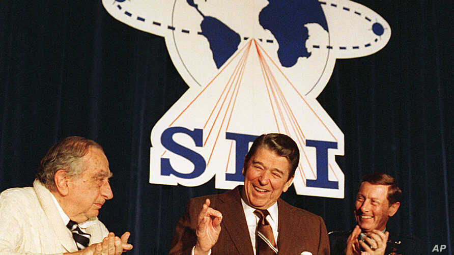 """FILE - U.S. President Ronald Reagan is flanked by physicist Dr. Edward Teller, left, and Lt. Gen. James A. Abrahamson, director of Strategic Defense Initiative, as he arrives to address a conference marking the first five years of his """"Star Wars"""" mis"""