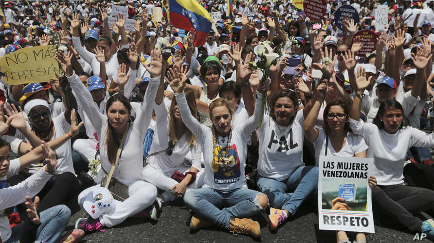 Lilian Tintori, front fourth from right, wife of jailed opposition leader Leopoldo Lopez, leads a sit-in blocking the Franciso Fajardo highway after a women march against repression was blocked from reaching the Interior Ministry in Caracas, Venezuel