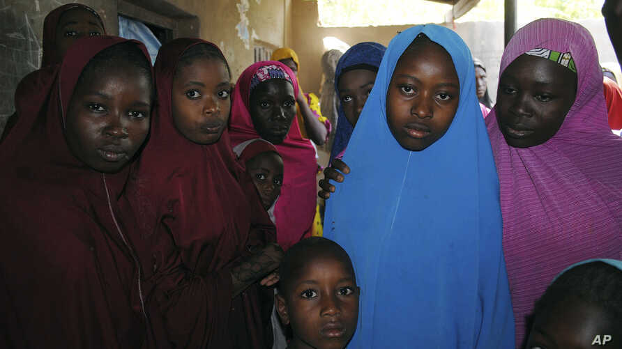 Aishat Alhaji , second, right, one of the kidnapped girls from the Government Girls Science and Technical College Dapchi who was freed, is photographed after her release, in Dapchi, Nigeria, March. 21, 2018.