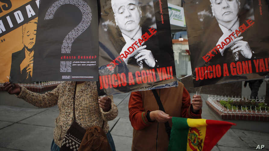 FILE - Activists holds signs depicting Bolivia's former President Gonzalo Sanchez de Lozada during a protest outside the US embassy in La Paz, Bolivia, Sept. 3, 2010.