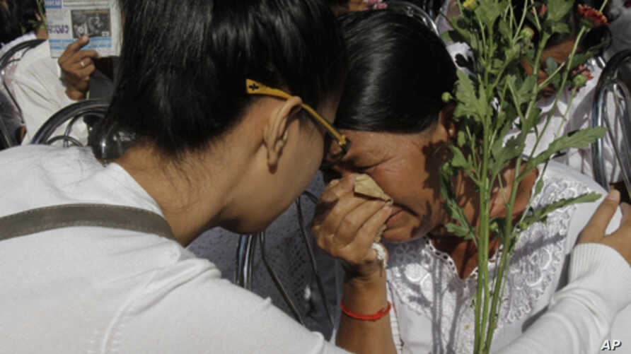 "A Cambodian Khmer Rouge victim, right, weeps during a Buddhist ceremony near Choeung Ek stupa, the site of the Khmer Rouge's former ""killing fields,"" on the outskirts of Phnom Penh, Cambodia, Sunday, Nov. 20, 2011."