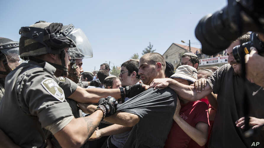 Young Israeli settlers scuffle with Border Police officers over the demolition of a building at the Jewish settlement of Beit El, near the West Bank town of Ramallah, July 29, 2015.