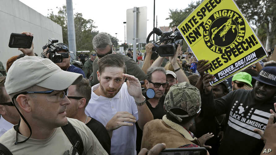 A supporter of white nationalist Richard Spencer, center in white shirt, tries to cover up as he clashes with the crowd after a speech by Spencer, Oct. 19, 2017, at the University of Florida in Gainesville.