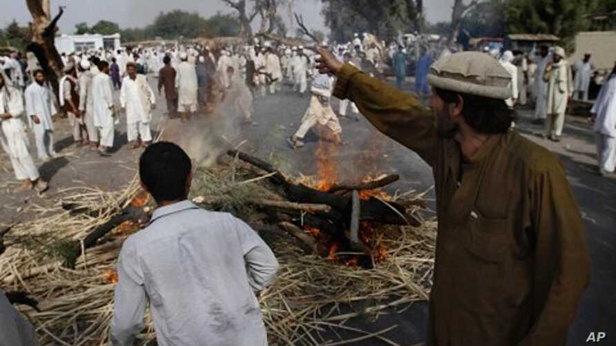 Afghan men from the Shinwari tribe stand near burning firewood set up as road blockade during a protest over a land dispute in Nangarhar province, east of Kabul, Afghanistan, August 10, 2011.