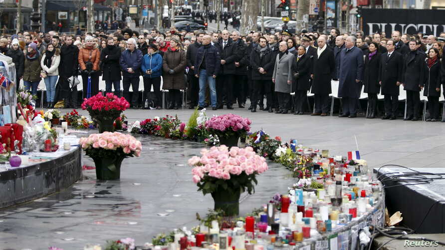 People attend a ceremony at Place de la Republique square to pay tribute to the victims of last year's shooting at the French satirical newspaper Charlie Hebdo, in Paris, France, Jan. 10, 2016.