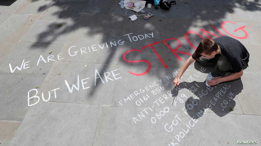 A man writes a message on the pavement in central Manchester, Britain, May 23, 2017.