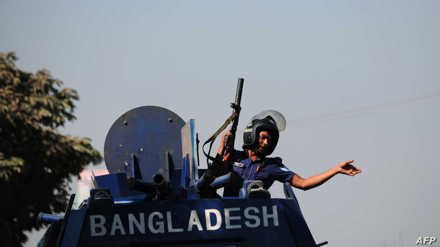 A Bangladeshi policeman gestures from an armored car after clashes with Bangladesh Nationalist Party (BNP) activists and its Islamist allies during a blockade in Aminbazer, in the outskirts of Dhaka, Nov. 26, 2013.