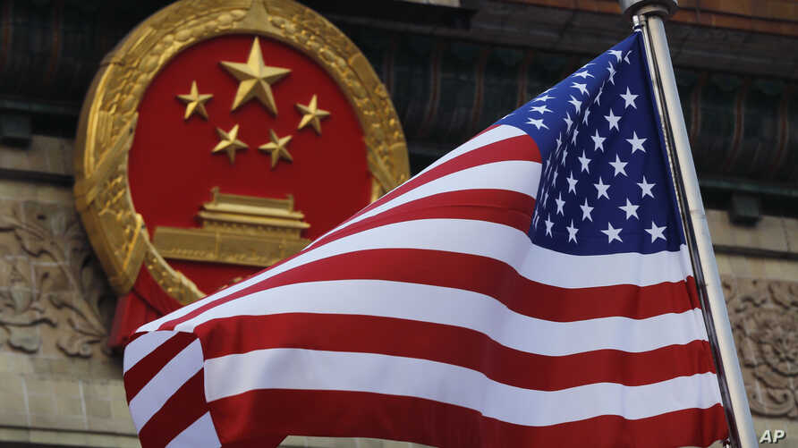 FILE - The American flag is flown next to the Chinese national emblem during a welcome ceremony for visiting U.S. President Donald Trump outside the Great Hall of the People in Beijing, Nov. 9, 2017.