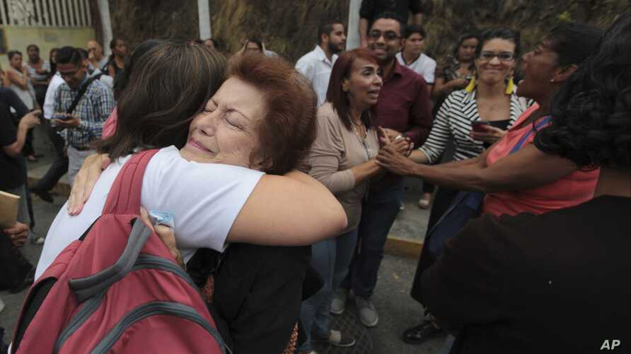 FILE - Relatives of political prisoners embrace as they wait for their release from the Heliciode prison in Caracas, Venezuela, June 1, 2018.