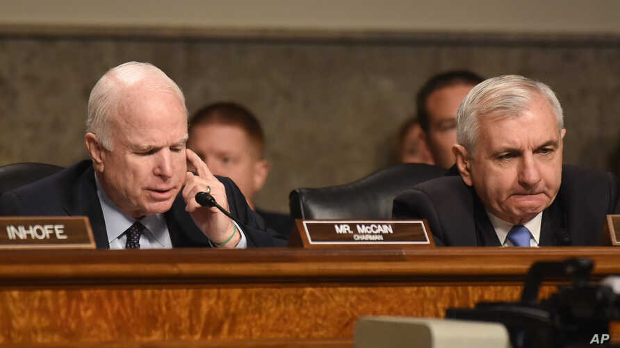 Senate Armed Services Committee Chairman John McCain, R-Ariz., left, accompanied by the committee's ranking member, Sen. Jack Reed, D-R.I., speaks during a committee meeting on Islamic State, on Capitol Hill in Washington, Oct. 27, 2015.