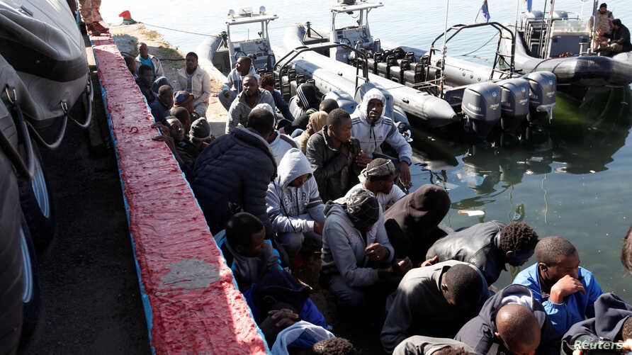 Migrants sit in a port, after being rescued at sea by Libyan coast guard, in Tripoli, Libya April 11, 2016.