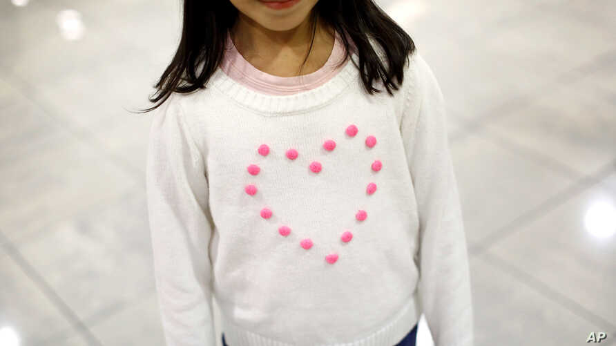 FILE - Janet Mejia, 7, wears a sweater emblazoned with a heart as she waits for her brother and sister to arrive from El Salvador at Baltimore-Washington International Airport in Linthicum, Md., Nov. 12, 2015. Her siblings were among the first teens