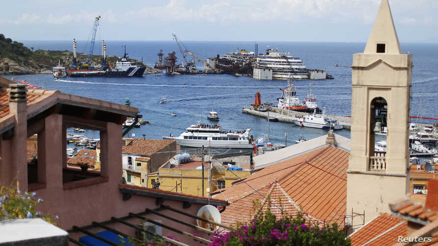 The Costa Concordia is seen over the rooftops at Giglio harbour, Giglio Island, July 13, 2014.