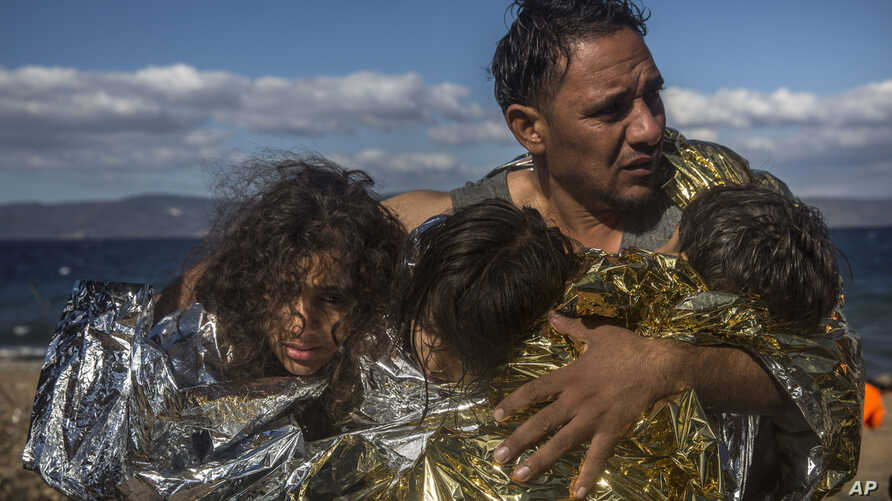 A man holds three children wearing thermal blankets after their arrival in bad weather from Turkey on the Greek island of Lesbos, Oct. 28, 2015.