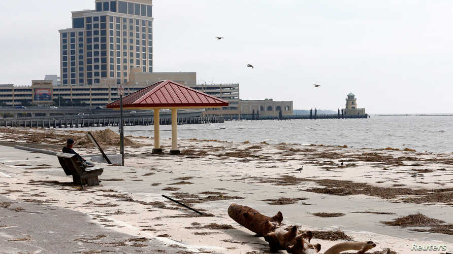 A man sits on a bench overlooking a beach covered in debris scattered by Hurricane Nate, in Biloxi, Mississippi, Oct. 8, 2017.