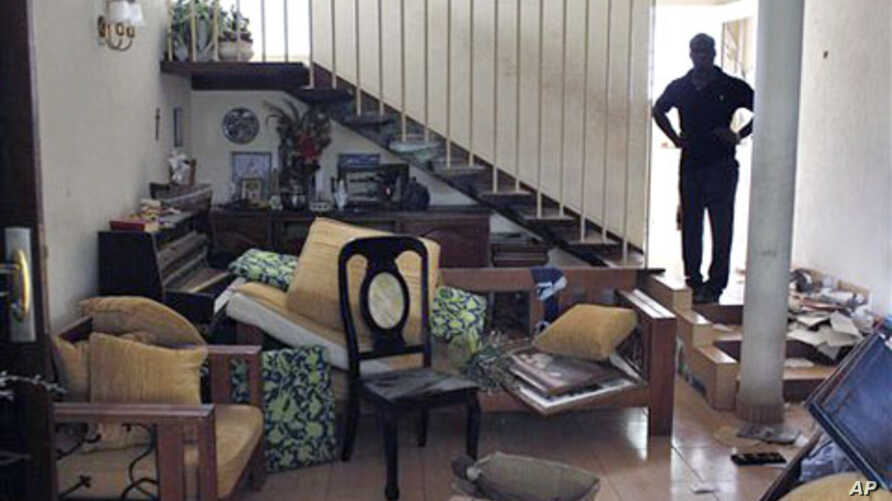 A relative stands in the looted home of Francois Konan Bany. Witnesses say dozens of armed militant youth loyal to Laurent Gbgabo tied up security guards, ransacked the home, and carried away everything of value, including kitchen appliances and air-