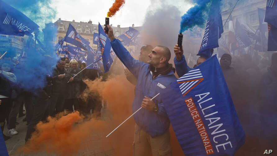 Police officers carrying union flags and flares gather outside the French justice ministry in Paris, part of police protests across France to demand better working conditions, Oct. 14, 2015.