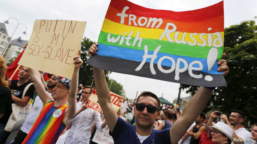 FILE - A group of Russian gays, seeking asylum in Germany because of their sexual orientation, take part in the annual Christopher Street Day gay parade in Cologne, Germany, July 5, 2015.